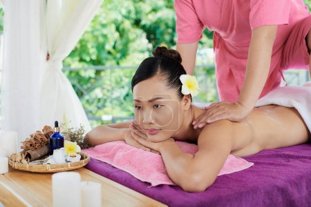Vietnamese attractive woman getting back massage and aromatherapy