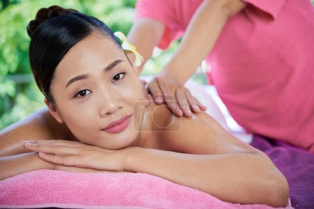 Young Asian woman having back massage with oils