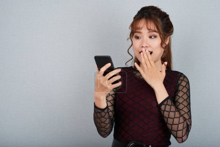 Shocked Vietnamese young woman reading message on smartphone