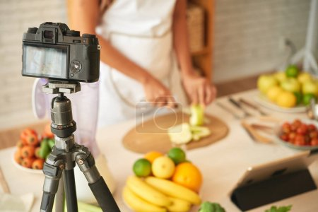 Woman shooting cooking process on digital camera