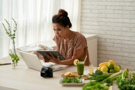 Young woman searching for recipe to cook for her blog