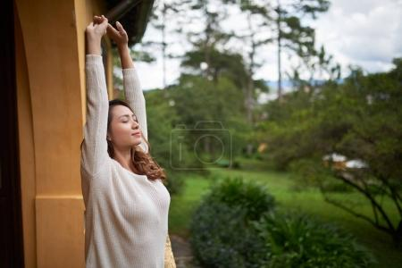 Beautiful Asian woman stretching in the morning on balcony of resort hotel