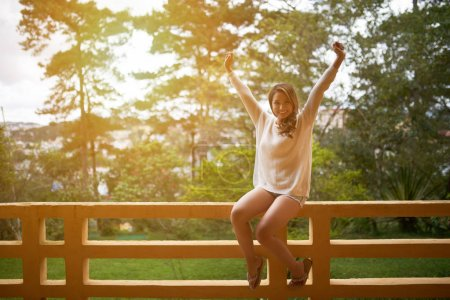 Happy Asian woman sitting on balcony railing in resort hotel and smiling at camera
