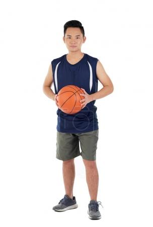 Full-length portrait of young Vietnamese basketball player with a ball