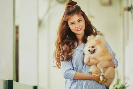 Portrait of beautiful young Asian woman with cute dog in hands