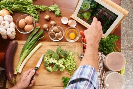 Man chopping ingredients for green smoothie. He is following recipe on tablet computer