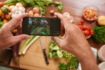 Man taking photo of cut vegetables on kitchen table