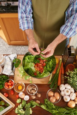 Cook adding parsley into the salad bowl, view from above