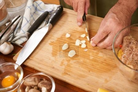Close-up image of hands chopping garlic to add in marinade