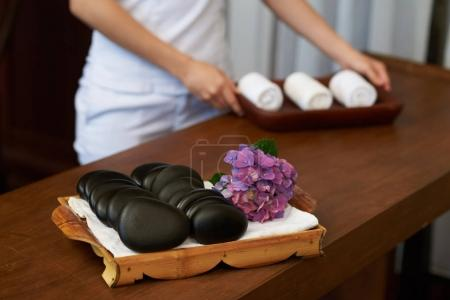 Cosmetologist preparing hot stones and fresh towels for the spa procedure