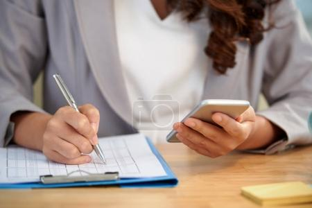 Close-up image of business woman checking phone and marking number in document