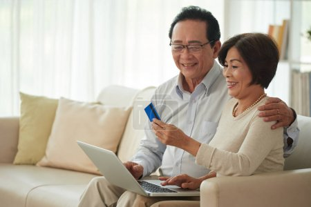 Senior smiling couple spending money on online purchase