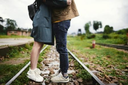 Photo for Cropped image of kissing couple standing on railway - Royalty Free Image