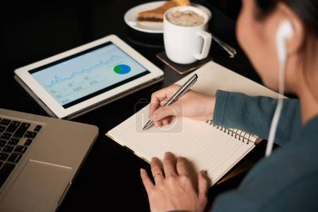 Financial manager analyzing report and taking notes
