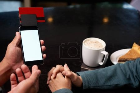 Waiter giving smartphone with credit card, enter pin code
