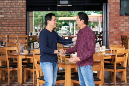 Photo for Laughing Vietnamese mature men shaking hands when meeting in the bar - Royalty Free Image