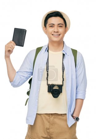 Happy young Vietnamese man with digital camera and passport