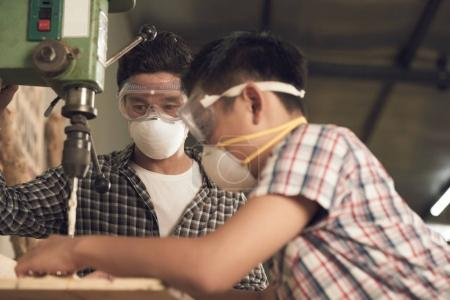 Vietnamese man looking how his son working with drill machine