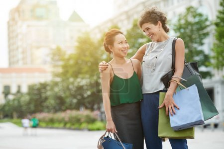 Cheerful multi-ethnic female friends hugging and talking outdoors