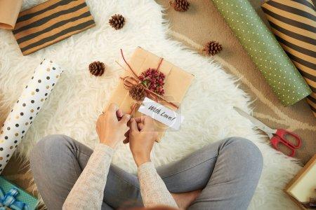 Photo pour Femme décorant boîte cadeau pour une personne qu'elle aime, vue d'en haut - image libre de droit
