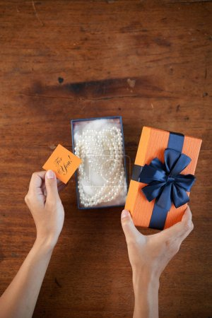 Hands of woman opening gift box with pearl necklace inside