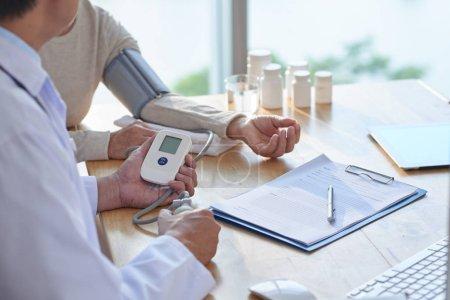 male doctor measuring blood pressure of elderly woman