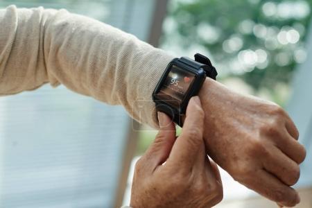 Photo pour Gros plan de la main féminine ridée avec un tracker de fitness moderne, fond flou - image libre de droit