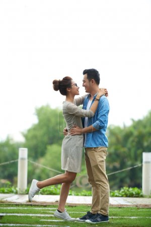 Portrait of young Asian couple embracing lovingly meeting for date in park