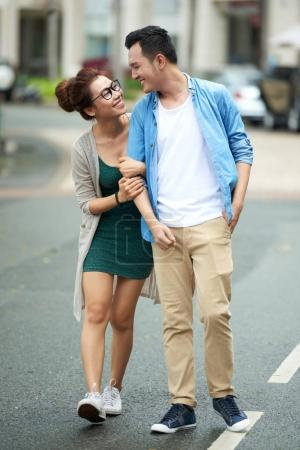 Portrait of young man and woman walking close together in street of big city and smiling looking at each other with love