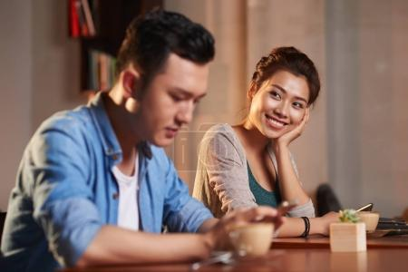 Portrait of smiling Asian woman looking at stranger man in cafe
