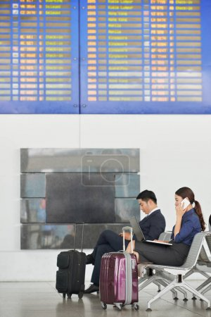 Side view portrait of modern Asian business people in airport with big suitcases