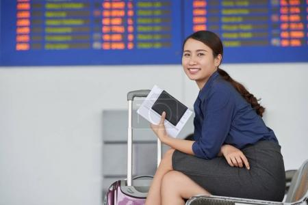 Side view portrait of smiling Asian woman looking at camera while waiting for departure in airport