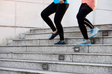 Photo for Legs of sportswomen running down the steps - Royalty Free Image