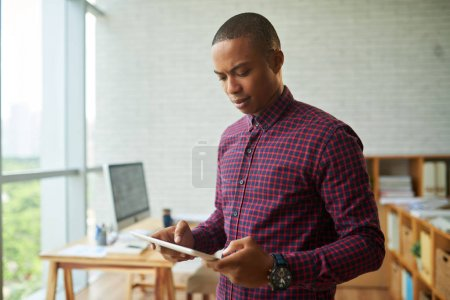 Afro-American businessman holding digital tablet while standing in modern office with panoramic windows