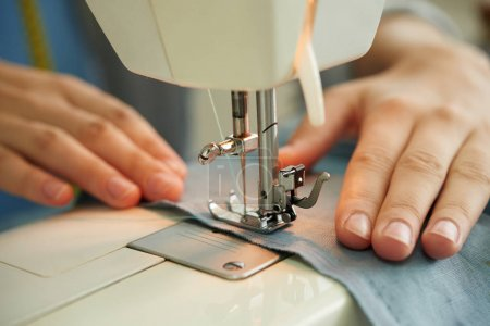 Photo for Hands of female tailor using sewing machine at work - Royalty Free Image