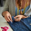 Постер, плакат: Close up image of woman sewing buttons on clothing item