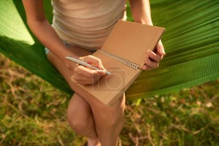 High angle view of woman taking necessary notes in diary