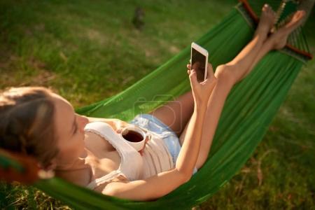 Photo pour Femme utilisant le téléphone portable tout en étant couché dans l'hamac dans le jardin vert - image libre de droit
