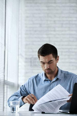 Serious entrepreneur reading business contract in office