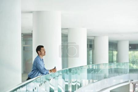 Pensive businessman with smartphone in hands standing on balcony in office building