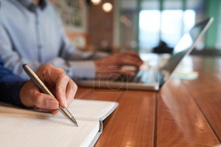 Photo pour Image en gros plan d'une femme d'affaires écrivant des plans et des idées dans son bloc-notes - image libre de droit