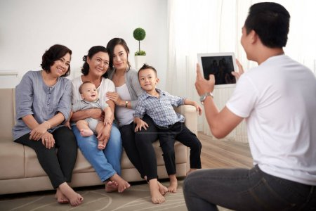 Portrait of big Asian family with two kids posing for photo at home
