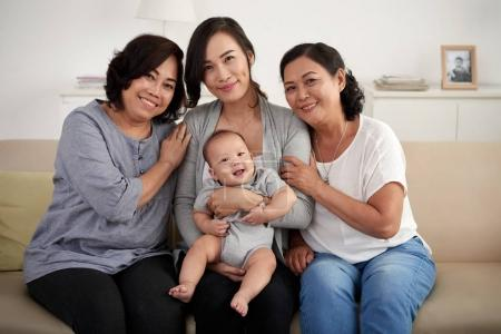 Portrait of three generations of woman in Asian family, posing on sofa at home smiling happily looking at camera Women in Asian Family