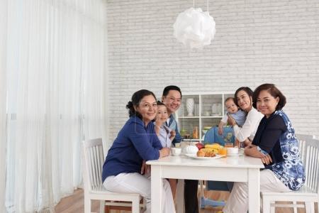 big Asian family gathering at dinner table and looking at camera