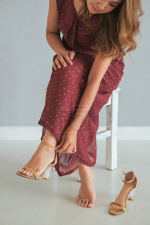 Cropped image of young Asian woman putting on heels