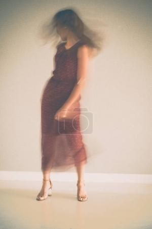 Young woman in summer dress dancing, blurred motion