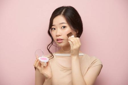 Portrait of pretty young Asian woman doing make-up