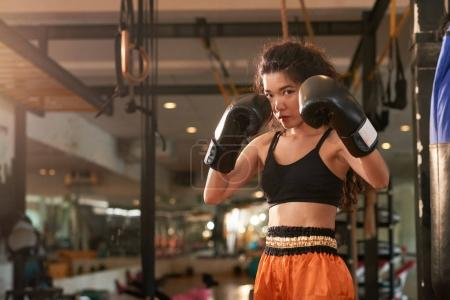 Photo for Female Muay Thai boxer is ready to hit - Royalty Free Image