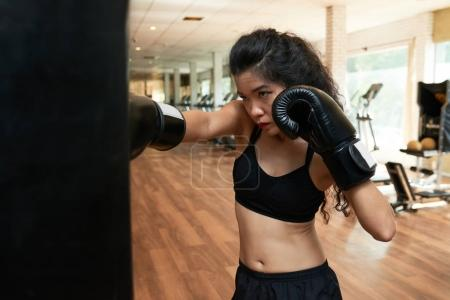 Portait of young woman in boxing gloves exercising in gym