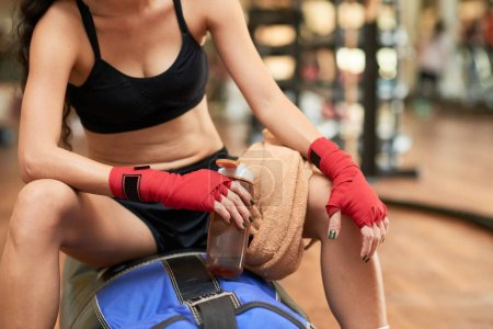 Female Muay Thai boxer resting after intense training